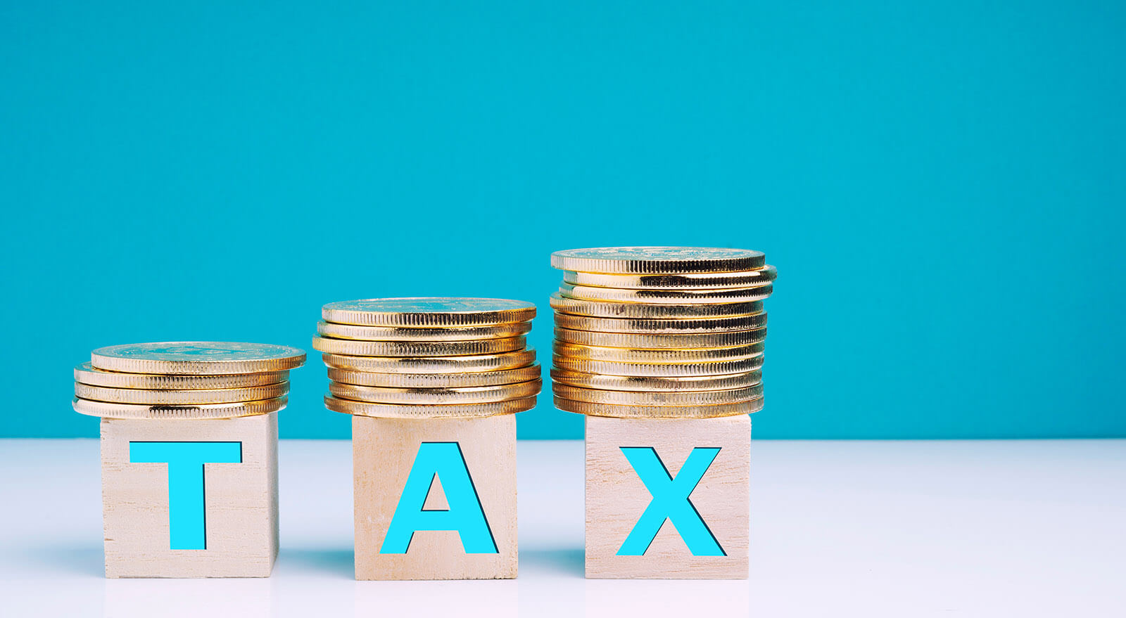 Tax Text On Wooden Blocks With Stacked Coins Over Table