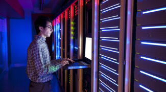 Modern interior of server room in datacenter. IT Engineer in Action Configuring Servers