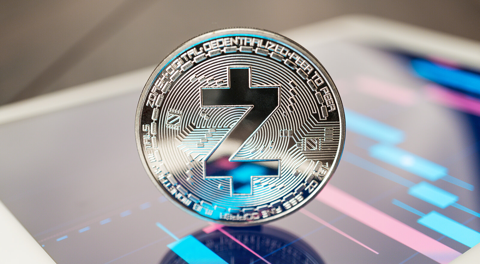 close-up photo of Zcash ZEC cryptocurrency physical coin on the tablet computer showing stock market charts. trading zcash cryptocoin concept on the wooden table
