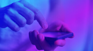 hands using smartphone closeup in neon colorful light
